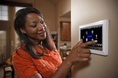 Woman using touch screen security system.