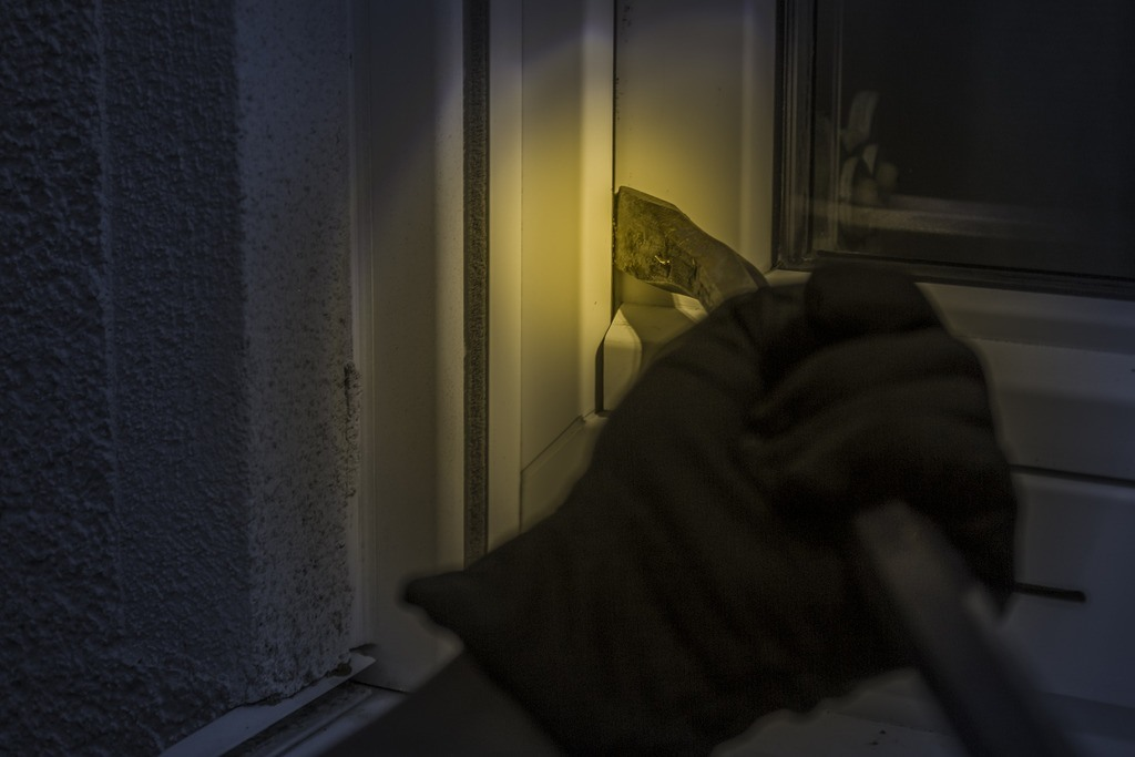 burglar opening window at night